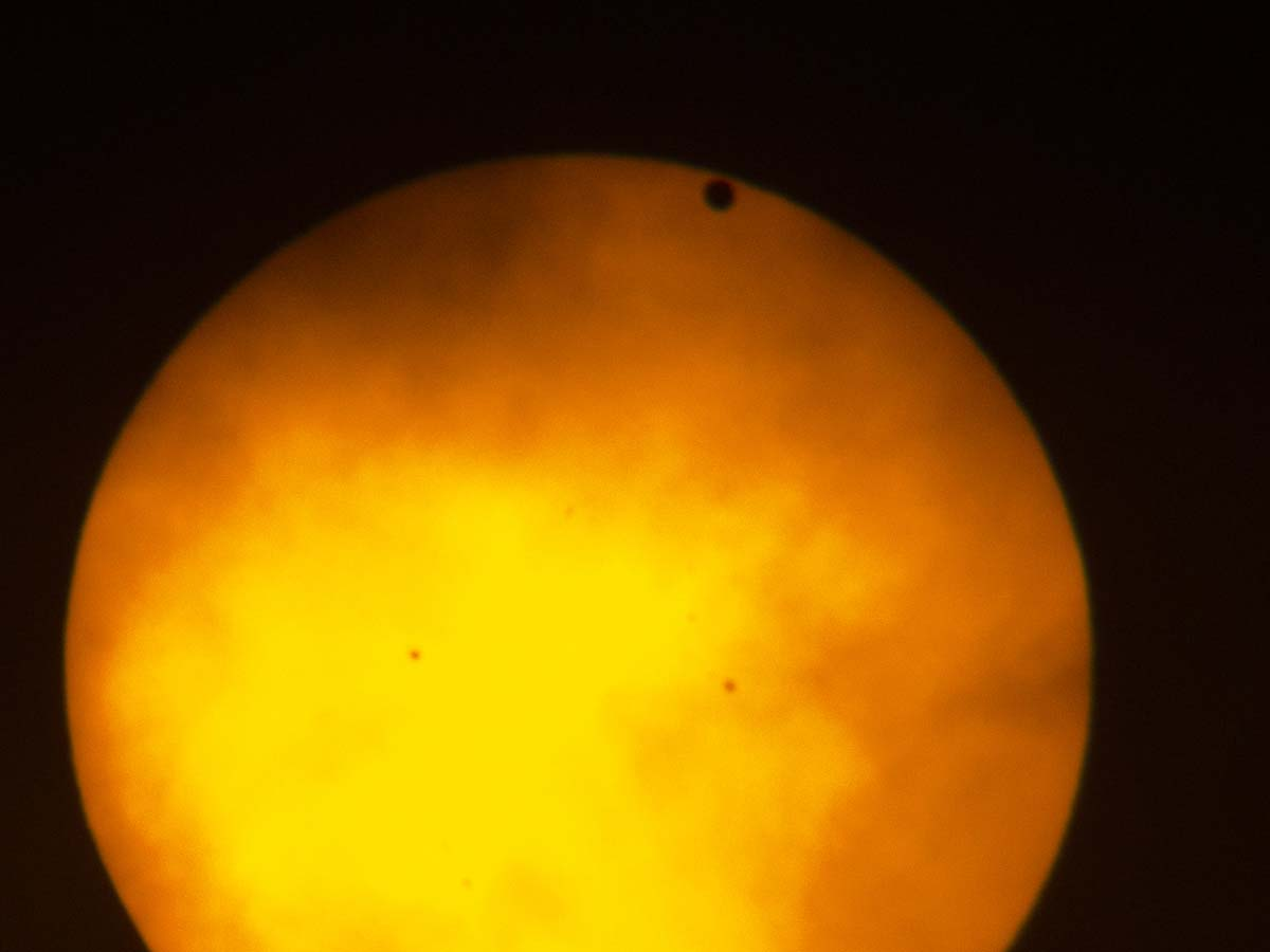 Transit of Venus, taken in New York City, June 5, 2012.  I was on extended assignment and didn't have my big scopes or camera, so I took this with a small handheld camera through my binoculars, which were covered by a solar filter.  I have some somewhat better photos from the 2004 transit.  Transits come in pairs separated by long gaps, so the next transit will not occur until 2117.