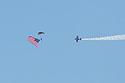 Skydiver brings in the flag, Sioux Falls Air Show, August 2019.  Lucas Oil stunt plane escorts him down.